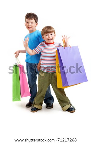 Portrait of two happy boys holding colorful bags over white background - stock photo