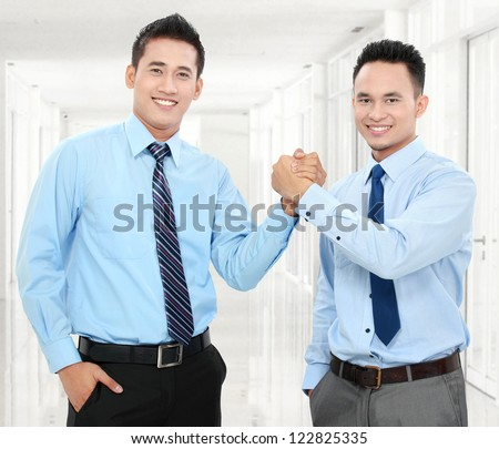 Portrait of two happy business men shaking hands with each other in office - stock photo