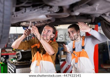 Portrait of two happy car mechanics at workshop. Focus on the left man - stock photo
