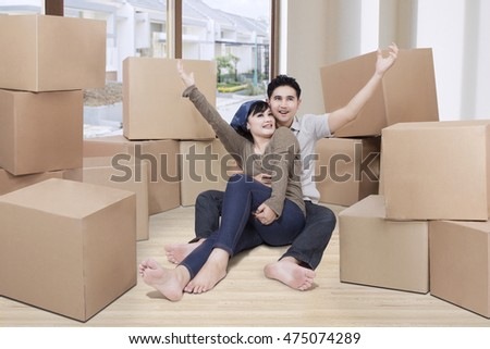 Portrait of two happy couple sitting on the floor with boxes in their new house