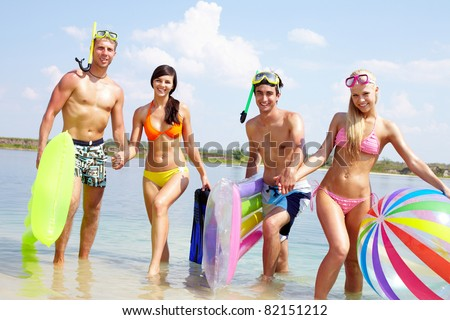 Portrait of two happy couples walking in water on summer vacation - stock photo