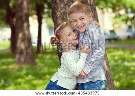 Portrait of two happy cute kids having fun in summer park - stock photo