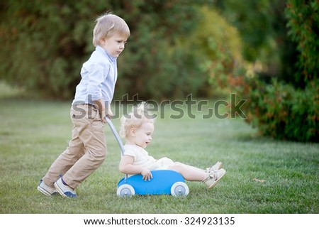 Portrait of two happy cute little siblings playing outdoors. Brother carrying his toddler sister in toy stroller, walking together in park in summer, having fun, full length - stock photo