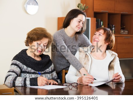 Portrait of two happy elderly women with papers and agency employee. Focus on girl - stock photo