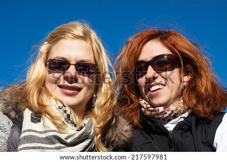 Portrait of two happy girlfriends over blue sky. - stock photo
