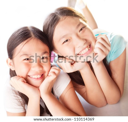 Portrait of two happy girls lying and looking at camera