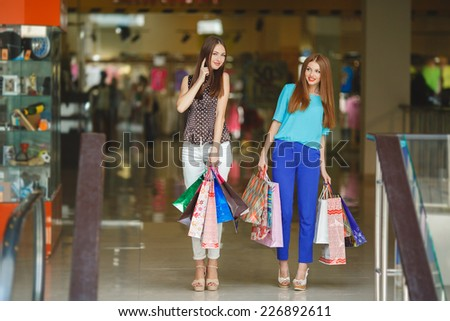 Portrait of two happy girls with paperbags looking at camera. Shopping together is fun. Two attractive young women holding shopping bags and smiling while standing in shopping mall - stock photo