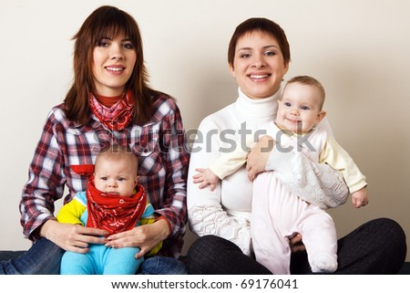 Portrait of two happy mothers with their little children