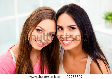 Portrait of two happy pretty young women at home