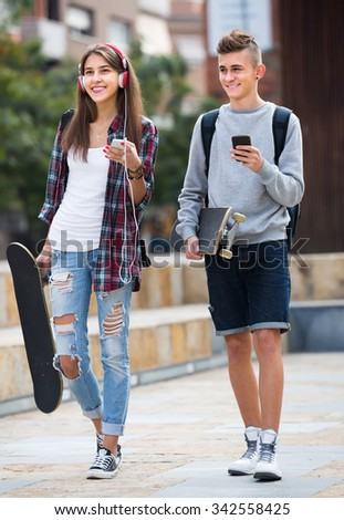 Portrait of two happy teenagers in casual with skateboards at the street  - stock photo