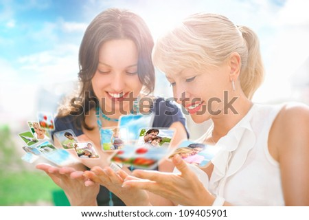Portrait of two happy women mother and daughter looking their photo and video files in social media resources using virtual interface of future. Outdoors at beautiful idyllic place.