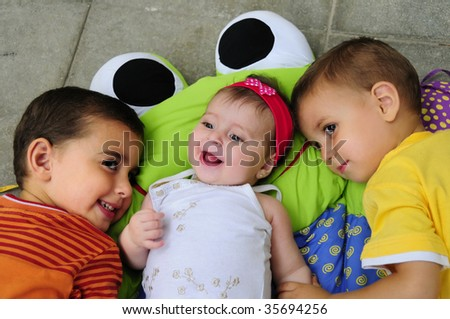 Portrait of two happy young boys with little baby girl - stock photo