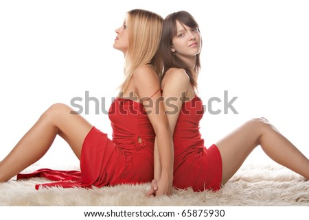 portrait of two happy young girlfriends sitting over white