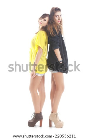 Portrait Of Two Happy Young Women Standing Back To Back Over White Background - stock photo