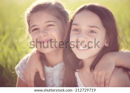 Portrait of two hispanic teens girls resting on meadow - stock photo