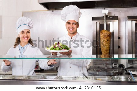 Portrait of two hospitable chefs with kebab at fastfood place - stock photo