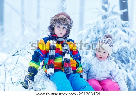 portrait of two kids: boy and girl in winter hat in snow forest at snowflakes background. outdoors winter leisure and lifestyle with children on cold days. - stock photo