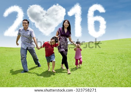 Portrait of two kids holding hands and running together with their parents on the field under cloud shaped numbers 2016