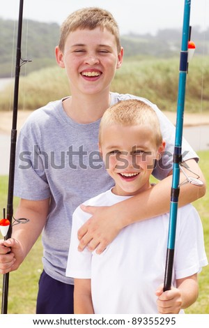 portrait of two little boys fishing by the lake - stock photo