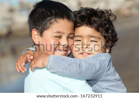 portrait of two little brothers hugging - stock photo