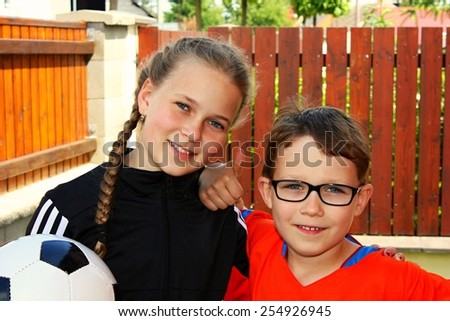 Portrait of two little children with a ball looking at camera and smiling, brother and sister - stock photo