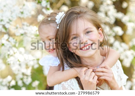 Portrait of two little girls girlfriends spring - stock photo