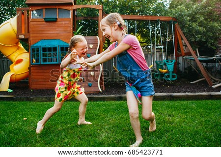 Portrait Of Two Little Girls Sisters Fighting On Home Backyard Friends Having Fun