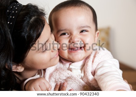 portrait of two little muslim girls, happy little girl holding her baby sister - stock photo