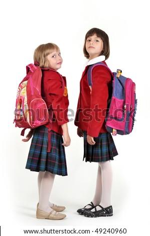 Portrait of two little schoolgirls with backpacks - stock photo