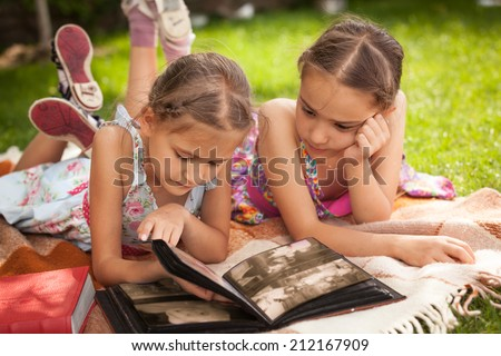 Portrait of two little sisters looking photo album at park - stock photo