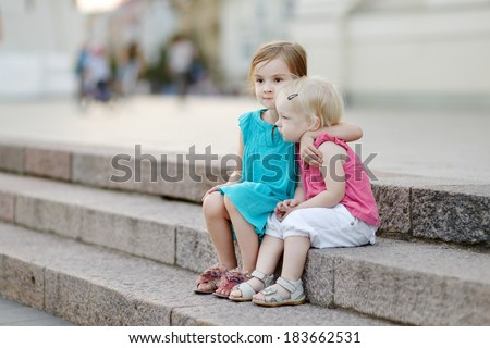Portrait of two little sisters outdoors at summer - stock photo