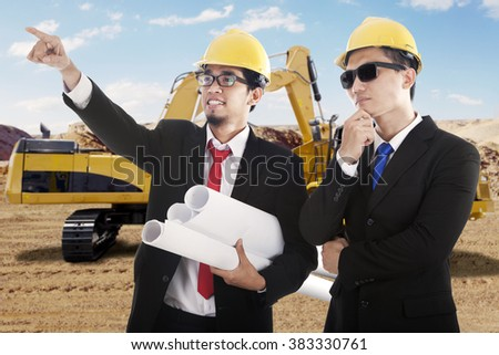 Portrait of two male engineers observe the construction site while wearing helmet and hold blueprint with excavator on the back - stock photo