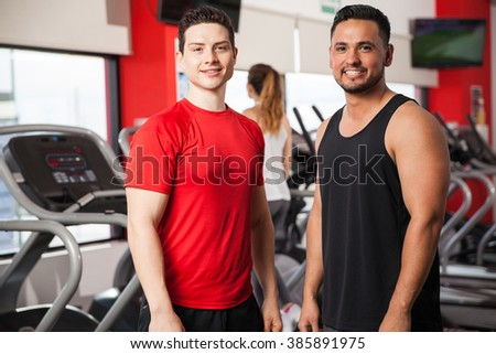 Portrait of two male friends in sporty clothing working out together in a gym and smiling - stock photo