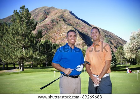 Portrait of two male golfers on the golf course - stock photo