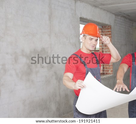 Portrait of two manual worker in new uniform Pair builder held on site paper plan Copy space for inscription on concrete wall - stock photo
