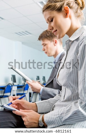 Portrait of two mature students sitting in the classroom - stock photo