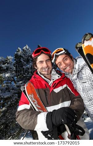 Portrait of two men at ski resort - stock photo