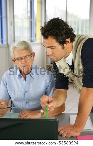 Portrait of two men in an office in front of a laptop computer - stock photo