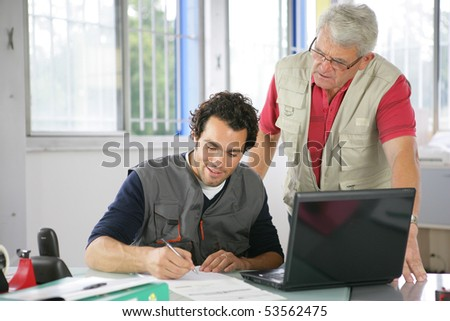 Portrait of two men in front of a laptop computer writing on a document - stock photo