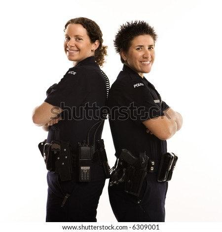 Portrait of two mid adult Caucasian policewomen standing back to back looking over their shoulders and smiling at viewer.