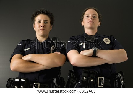 Portrait of two mid adult Caucasian policewomen standing with their arms crossed looking at viewer with serious expressions.