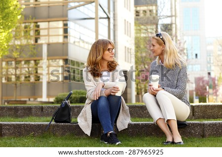 Portrait of two middle age women sitting at office park while on coffee break. Businesswomen relaxing while drinking coffee and chatting with each other.  - stock photo