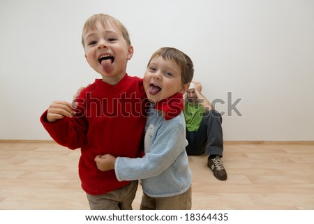 Portrait of two noisy children being naughty, with adult in background sat on floor covering his ears. - stock photo