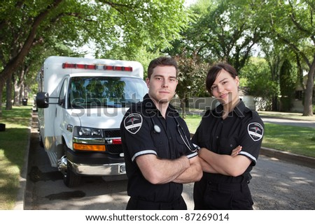 Portrait of two paramedics standing in front of ambulance vehicle - stock photo
