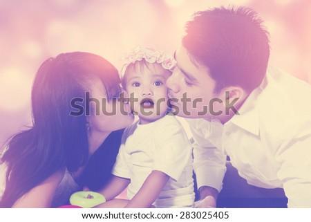 Portrait of two parents kiss their little daughter with defocused lights background - stock photo