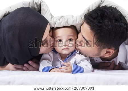 Portrait of two parents lying on the bed while kissing their baby boy under a blanket - stock photo