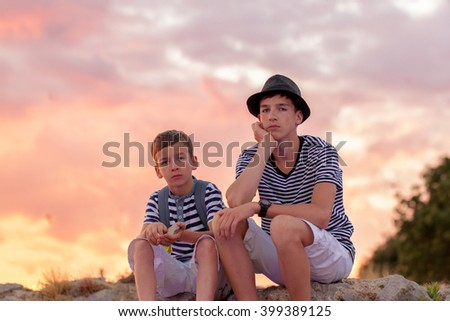 Portrait of two pensive beautiful brothers on backdrop of sunset sky, outdoor, Italy. - stock photo