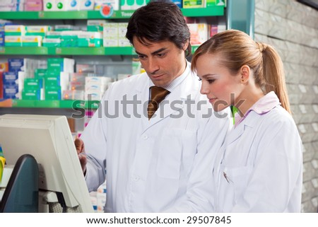 portrait of two pharmacists looking at computer monitor - stock photo
