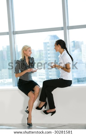 Portrait of two pretty colleagues drinking tea and chatting with each other - stock photo
