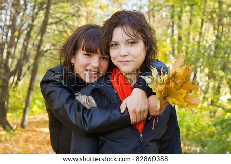Portrait of two pretty girls  at autumn park - stock photo